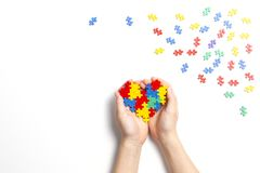 Child hand holding colorful heart on white background. World autism awareness day concept. Kid hand holding colorful heart on white background. World autism stock photography