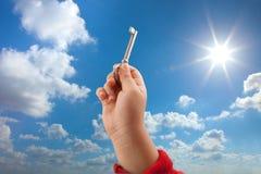 Kid hand holding key. Child hand holding key on sunny sky background Royalty Free Stock Image