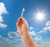 Kid hand holding key. Child hand holding key on sunny sky background Stock Image