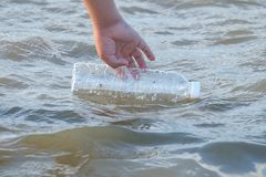 A kid hand keeping a plastic bottle of drinking water from sea beach stock photography