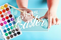 Kid hand painted boiled Easter eggs, paints and brushes on a blue background. Preparation for the holiday. Girls hands draw a royalty free stock photo