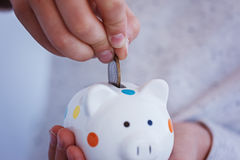 Kid hand putting coin into piggy bank or money box. Stock Photo