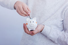 Kid hand putting coin into piggy bank or money box. Royalty Free Stock Photo