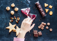 Kid hand reaching for sweets - happy childhood dream. Kid hand reaching for different types of sweets displayed on black background - happy careless childhood or Stock Images