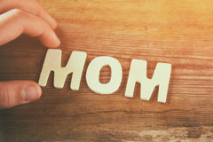 Kid hand spelling the word MOM made with block wooden letters on wooden background. vintage filtered and toned Stock Photography