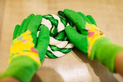 Kid hands in gloves making caramel sweets. In workshop. Holiday fun in candy store. Lollipop preparation process Royalty Free Stock Images