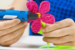 Kid hands holding blue 3d printing pen and making new item. Kid hands holding 3d printing pen and making new item Royalty Free Stock Photo