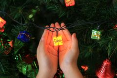 Kid hands holding magic gift from Christmas decorative. Merry Christmas and Happy New Year concept royalty free stock photos