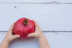Kid hands holding Red Pomegranate on wooden background royalty free stock image