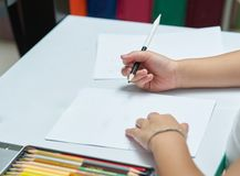 Kid Hands holds color pencil and think about writing things on w Stock Photos