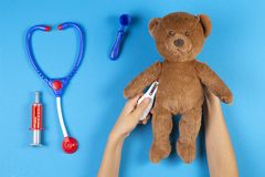 Free Kid Hands Measuring Temperature With Toy Thermometer Of Teddy Bear, Toys Medicine Tools On Light Blue Background. Top Royalty Free Stock Photos - 160618098