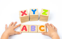 Kid hands playing wooden alphabets block Royalty Free Stock Image