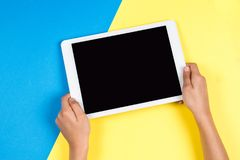 Kid hands with tablet computer on blue and yellow background.  royalty free stock image
