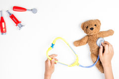 Kid hands with toy stethoscope, teddy bear and toy medicine tools on a white background. Top view. Stock Photo