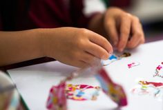 Kid hands view ,playing sticker of cartoon toy stock images