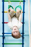 Kid hanging on gymnastic rings Royalty Free Stock Photo