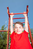 Kid hanging from a jungle gym Stock Photos