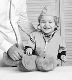 Kid with happy face plays doctor. Health and childhood concept Little assistant examines teddy bear. Male hand holds. Bear and boy in medical gown holds stock photo