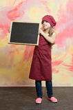 Kid, happy girl cook in red chef hat, apron Stock Image