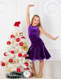 Kid happy because holiday season arrive. Family holiday concept. Girl velvet dress feel festive near christmas tree. Make this day best holiday ever. Winter royalty free stock photography