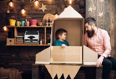 Kid happy sit in cardboard hand made rocket. Boy play with dad, father, little cosmonaut sit in rocket made out of. Cardboard box. Rocket launch concept. Child stock photos