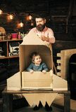 Kid happy sit in cardboard hand made rocket. Parenthood concept. Boy play with dad, father, little cosmonaut sit in. Rocket made out of cardboard box. Child boy royalty free stock photos
