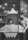 Kid happy sit in cardboard hand made rocket. Parenthood concept. Child cute boy play cosmonaut, astronaut. Boy play with. Dad, father, little cosmonaut sit in royalty free stock photography