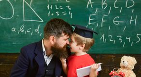 Kid happy studies individually with father, at home. Individual schooling concept. Father with beard, teacher teaches. Son, little boy. Teacher and pupil in stock images