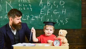 Kid happy studies individually with father, at home. Individual schooling concept. Teacher and pupil in mortarboard. Chalkboard on background. Little boy shows stock photo