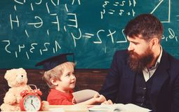 Kid happy studies individually with teacher, at home. Individual schooling concept. Father with beard, teacher teaches. Son, little boy. Teacher and pupil in royalty free stock photos