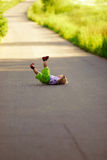 Kid has fallen to path. The little girl has not learnt to go well yet and has failed on asphalted footpath. The child has not suffered Royalty Free Stock Photography