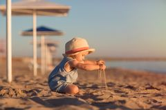 Kid in a hat playing with sand on the beach by the sea. holidays with children near the ocean. Baby under beach umbrella royalty free stock photography