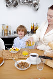 Kid having breakfast with his mother Stock Photos