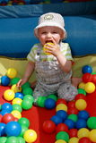 Kid having fun. Baby boy laughing at the ball castle surrounded by colored balls Stock Image