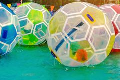 Kid having fun in giant bubble ball on water in the swimming pool at the theme park stock photography