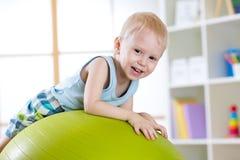 Kid having fun with  gymnastic ball Royalty Free Stock Photos