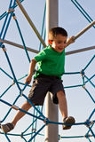 Kid having fun on the jungle gym at the park stock photography