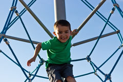 Kid having fun on the jungle gym at the playground Royalty Free Stock Photo