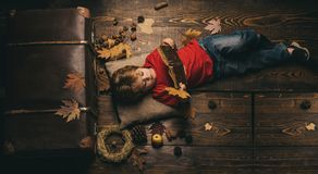 Kid having fun with Leaf fall. Kid playing in autumn. Little cute boy lies on a wooden floor with autumn leaves and read stock photography