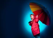 Kid having fun with Leaf fall. Raining kids. Cheerful boy in raincoat with colorful umbrella. Funny face. Cloud rain stock photo