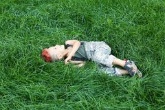 Kid having fun outdoors..A little boy with red hair.Child in uniform. The child indulges, croaks. The boy lies on the grass Royalty Free Stock Images