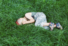 Kid having fun outdoors..A little boy with red hair.Child in uniform. The child indulges, croaks. The boy lies on the grass Royalty Free Stock Image