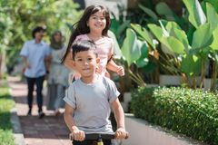 Kid having fun with sister riding a bike. Happy young kid having fun with sister riding a bike Royalty Free Stock Image