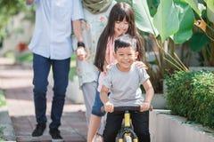 Kid having fun with sister riding a bike. Happy young kid having fun with sister riding a bike Royalty Free Stock Photo