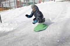 Kid having fun on sled. Kid having fun on his sled in winter Stock Photography