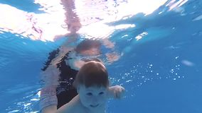 The child dives under the water in the pool. Kid having fun in swimming pool. Underwater portrait of child. Summer vacation stock video