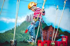 Kid having a good time and having fun at an adventure playground with diferent activities. Happy childhood concept. Little kid having a good time and having fun royalty free stock image