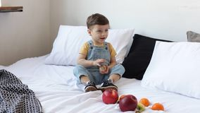 Kid having a table full of organic food. Cheerful toddler eating healthy salad and fruits. Baby choosing between apples, bananas, stock video footage