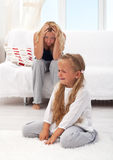 Kid having a tantrum. Little girl having a temper tantrum with her desperate mother in background royalty free stock photos