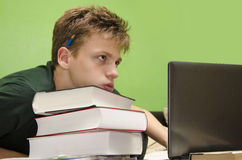 Kid having to much homework. Tired kid, has too much homework, closeup of exhausted boy, resting head on pile of books royalty free stock image